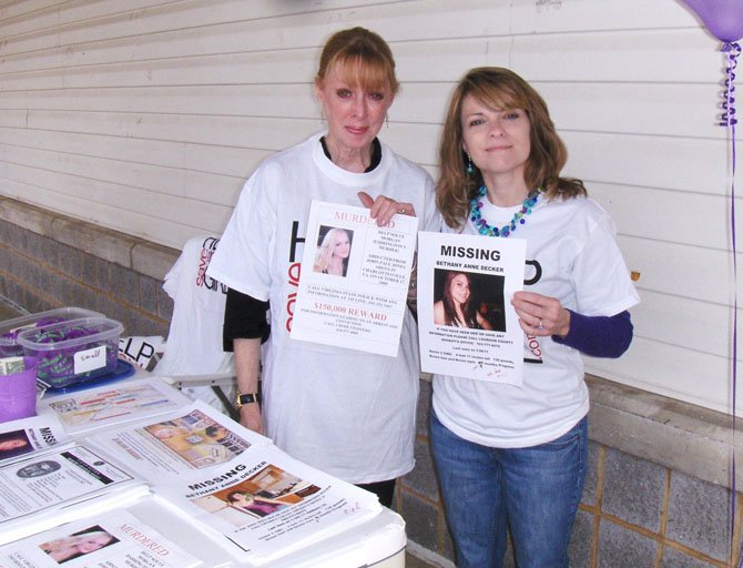 (From left) Gil Harrington and Kim Nelson hold posters with their daughters' photos and pass out information to local residents.