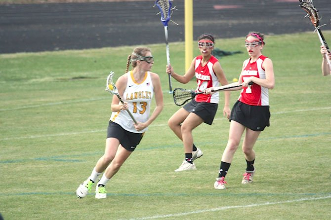 Langley High junior midfielder Hayley Soutter (13) goes to the goal during the Saxons' Liberty District home girls' lacrosse game versus McLean on March 28. Mackenzie May, a senior midfielder, is the Highlander on the right.