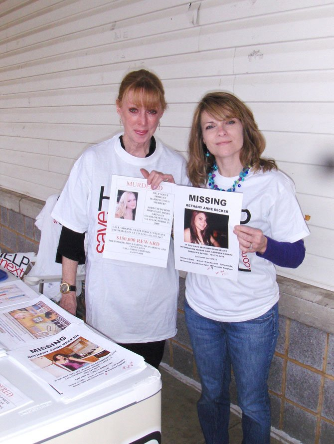 Gil Harrington (left) and Kim Nelson hold posters with their daughters' photos and pass out information to local residents.