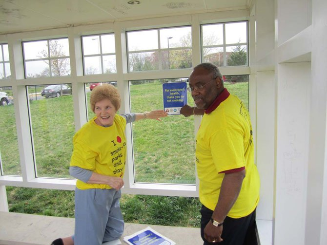 "Councilwoman Del Pepper and Mayor Bill Euille place the first ""Thank you for not smoking"" sign on a City bus shelter."