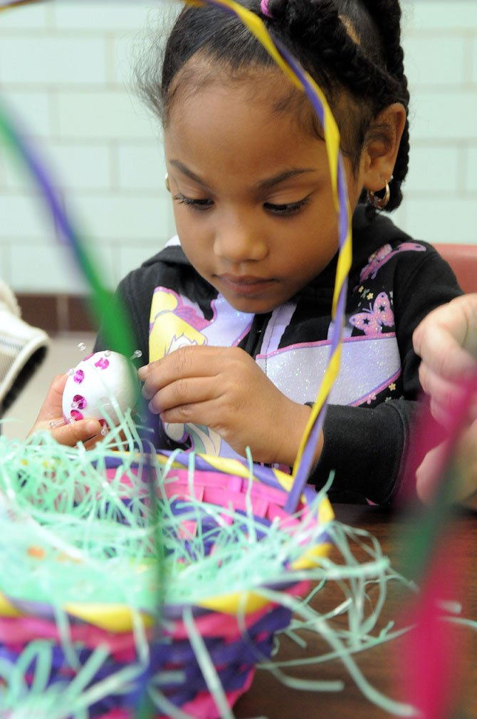 Five-year-old Amirah works on creating a jeweled egg with sequins and colored stones at the Gum Springs Community Center on Saturday, April 7.