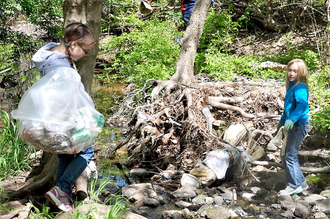 From left, Claire Jonas, 10 and Meg Anderson, 9, pick up trash along a stream bed near downtown Herndon Friday, April 6.
