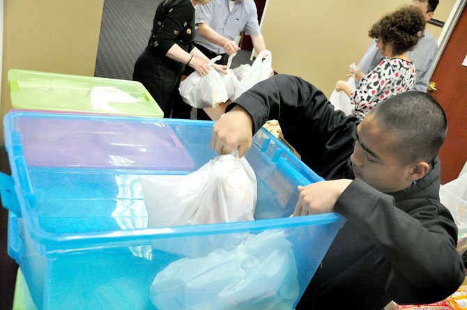 Patrick Francisco, a volunteer with Helping Hungry Kids, packs bagged meals for needy children into containers during the groups weekly meal packing event Thursday, April 5. 