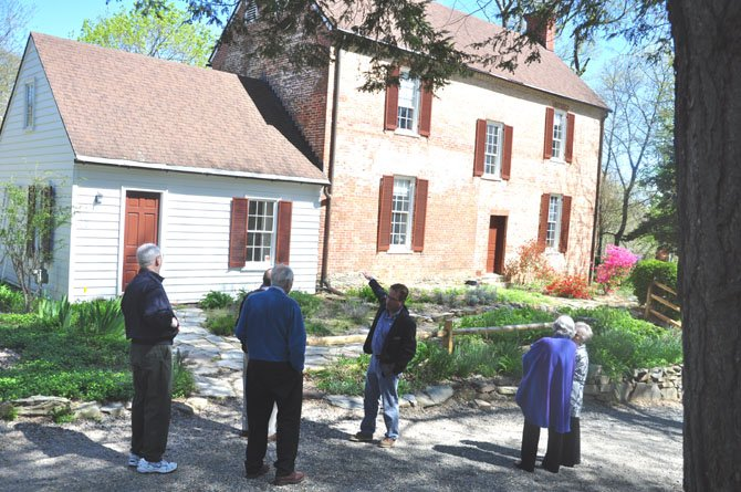 Mike Henry, manager of Colvin Run Mill, points out the miller's house on a tour of the grounds.