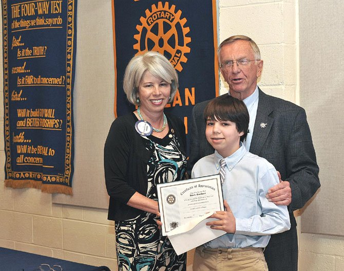 Noah Haefner, a seventh grader at Longfellow Middle School, received a Certificate of Appreciation from the Rotary Club of McLean for helping to raise $2,600 for the McLean Stop Hunger Now project. Noah (center) with McLean Rotary President Cherry Baumbusch (left) and Bob Hahne (right), a McLean Rotarian and an organizer of the McLean Stop Hunger Now project.