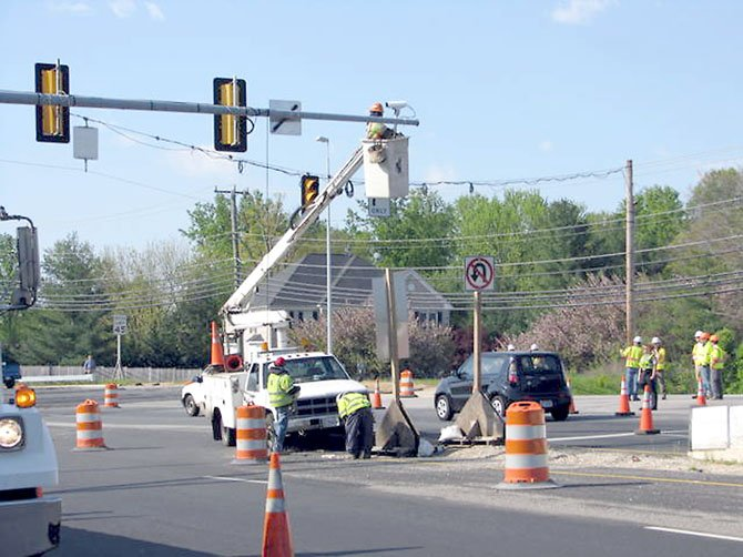Workers remove the traffic signal on the Fairfax County Parkway Tuesday, April 10, to make way for the new overpass that is part of the last phase of the Fairfax County Parkway project.