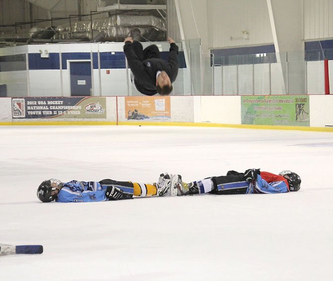 Nationally renowned figure skater Michael Weiss does a back flip over his son, Reston Raider player Chris Weiss, and teammate John Cardellicchio, as a reward for the local teams' having qualified for and being a part of the  12-under Tier II National Ice Hockey Championships.