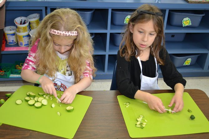 Kindergarten students at Norwood School in Bethesda/Potomac cut produce to make a vegetable pizza. Experts say cooking classes can boost self-confidence and enhance social skills.