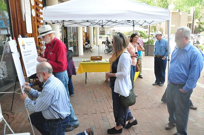 Reston residents line up to sign Reston founder Robert Simon's birthday card in front of the Reston Museum Saturday, April 14.