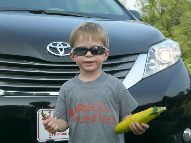 Hunter Basile, 3, holds vegetables that will be donated to Share.