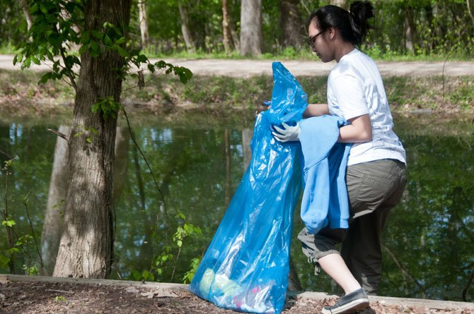 Nadya Rizkia, 16 years old student at Northwest HS, picks up trash along the path bordering the C&O Canal.