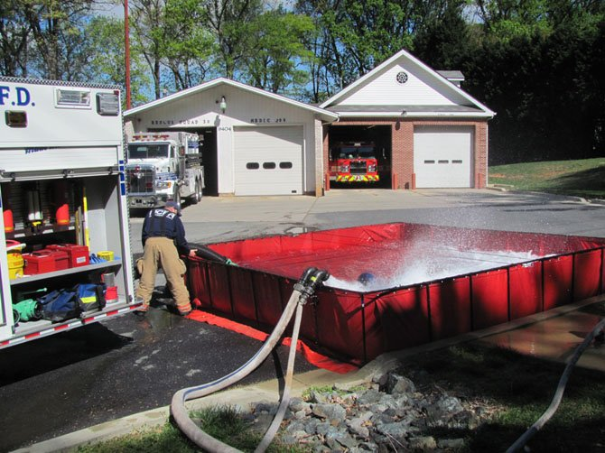 Part of training to be a fire engine driver is to learn how to manage the rural water supply loop. Here on Friday, April 13, career firefighters at Cabin John Volunteer fire department practice using the tanker truck and fire hydrant for filling and drawing water. The 3,500 gallon tanker trucks and the water containers create a water supply for fighting fires in areas that have no hydrants.