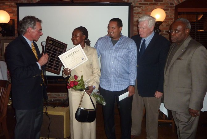 Community Lodgings board chairman Chris McMurray, left, presents Harriet Owusu with the Outstanding Achievement Award as her mentor, Besu Feleke of BB&T Bank, U.S. Rep. Jim Moran and Mayor Bill Euille look on.