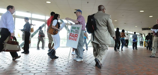 David McCracken of Oak Hill hands out literature to passengers debarking from the Springfield/Franconia Metro.