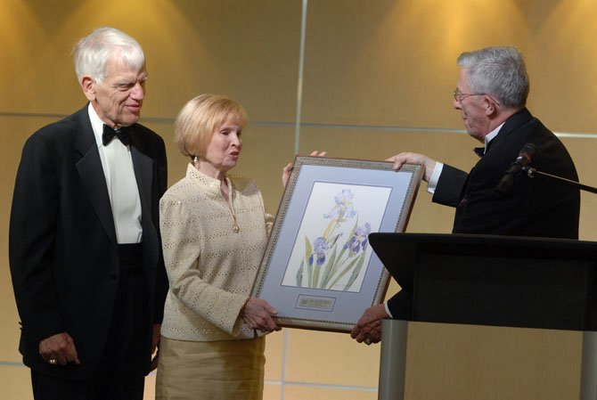 Former City of Fairfax Mayor John Mason presents a gift to retiring George Mason University President Alan Merten and his wife, Sally, at the City of Fairfax Mayor's Ball on Friday evening. The Mertens were honorary co-chairs for the event, to honor their service to the Fairfax community and for the arts.