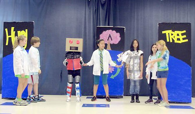 During the Earth Day Assembly, Churchill Road 6th graders Eliza Young, Austin Barre, Lucas Gaitan, Linda Diaz, Katherine Lan, Schuyler Leffler and Anneke Noe perform a skit about scientists who make a robot out of recycled materials.