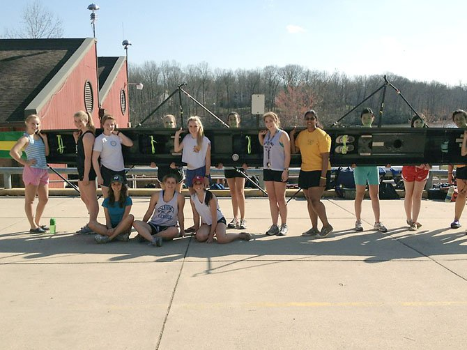Some of the Langley women crew members displaying one of the boats that was re-laced in a show of support for Coach Hess.