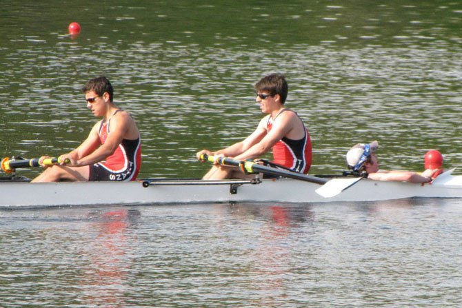 With Mark Comey in the coxswain seat, rowers Greg Montenegro, left, and Henry Anderson, right, help power the T.C. Williams boys varsity 4 crew team toward the finish line in their morning heat at the Smokey Jacob Regatta on April 21. The varsity 4 won the heat and then took second place in the final, finishing just .62 seconds behind the winner.