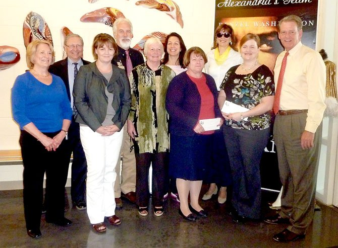 Executive Director Ann Dorman, left, joins First Night Alexandria board members April 19 in presenting checks to support local school music programs.