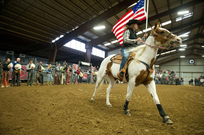 On Saturday April 28, a horsewoman trots an American flag around the indoor arena at Frying Pan Park at the start of the Professional Bull Riding event co-sponsored by the Friends of Frying Pan Park and the Fairfax County Park Authority. Dozens of bulls and riders entertained a sold-out crowd of 1,200 fans with their feats of athleticism.