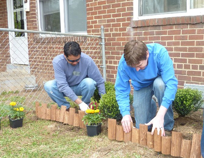 Jude Salac and Justin Domire of the Structural Engineers Association team do landscaping work for the front garden of a home on Edison Street.
