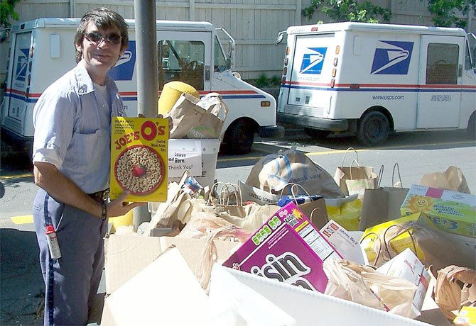 Kevin Martucci shows off the food collected for the upcoming Stamp Out Hunger Food Drive on May 12.