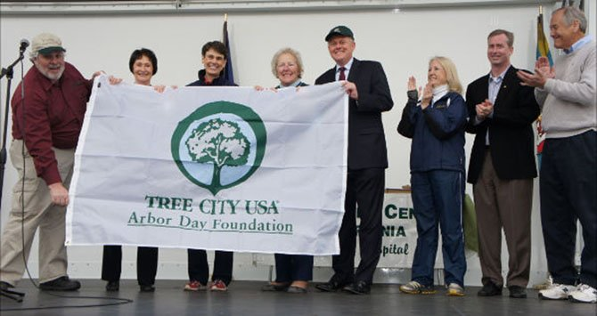 Fairfax County does it again – from left: The 2012 Tree City USA Banner is unfurled by Jim McGlone of the Dept. of Forestry, Sharon Bulova, Chairman of the Fairfax County Board of Supervisors (D-At-Large), Supervisor Linda Smyth, Providence District, Supervisor and Vice Chairman Penny Gross, Mason District, Supervisor John Cook, Braddock District, Virginia General Assembly Delegates, Vivian Watts, (D-39) and David Bulova (D-37) and State Senator David Marsden (D-37).