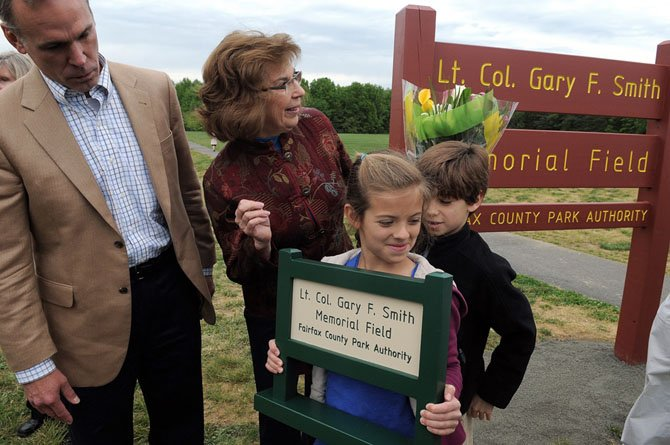 Director of the Fairfax County Park Authority John W. Dargle Jr. presents Ann Smith and her family with a replica of the new sign designating Field #5 at the Lt. Col Gary F. Smith Memorial Field.