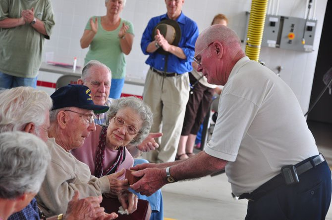Past Great Falls Volunteer Fire Chief Homer Johns presents Milburn Sanders, who joined the department 70 years ago, with a brick from the original station Saturday, May 5.