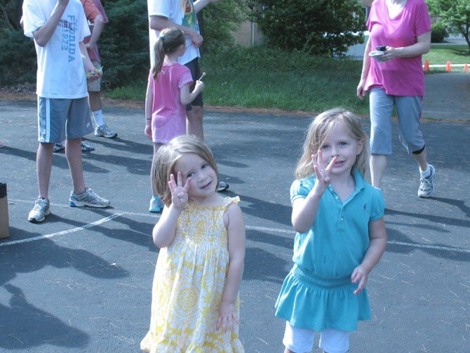 Two 3-year-olds, Emmy Brilliant and Grace Riihimaki. hold up four fingers when asked how many laps each of them did.