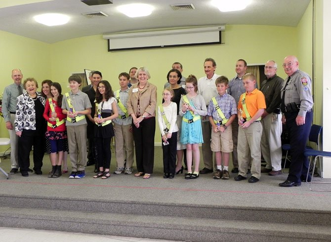 Safety patrol awardees (front row) with Woman's Club education co-chair Catharine Stroemer (far left), county police school resource officer Tom Harrington (far right) and Woman's Club president Ginny Sandahl (center); parents and supporters are behind.