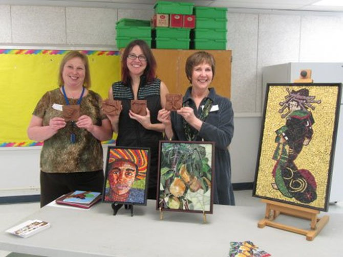 Flanked by mosaic artists Andrea Shreve Taylor and Bonnie Fitzgerald, Churchill Road art teacher Jenny Whiteman displays the tile samples for the second grade's outdoor tile wall highlighting the four stages of the Monarch butterfly life cycle and the project kick-off meeting in February.