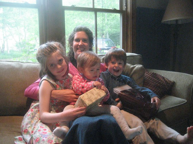 Elizabeth Rees with children Sophia (now 8), Dylan (now 5) and Maya (now 2). This picture was taken on Pentecost last year. I'm a priest, and this picture is taken after church. I was exhausted and relaxing on the couch, and all the kids came over to snuggle with me.