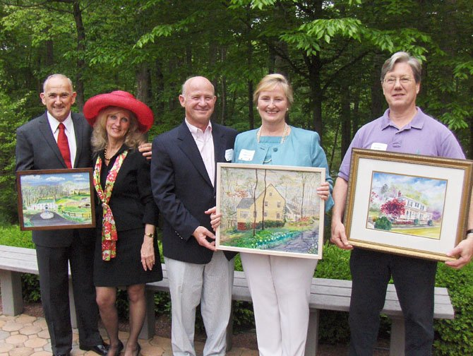 From left: Rob Airaghi, Lynne Garvey-Hodge, Joe and Vickie Luchini and Brant Baber hold the paintings of their homes done by artists Trudi Arnold and Peggy Cranston. They were honored Sunday at a homeowners' reception at the Fairfax Station home of Sharon and Mark Gottlieb. (Not pictured are Kathy Kalinowski and Lisa and Paul Brockman).