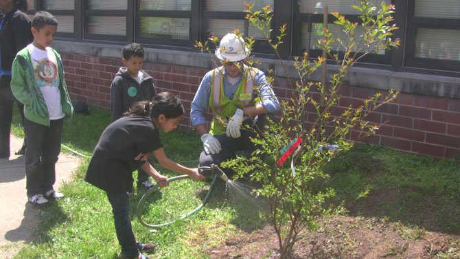 Dominion Groundman, Joe Jonkman, helps a student water a newly planted tree.