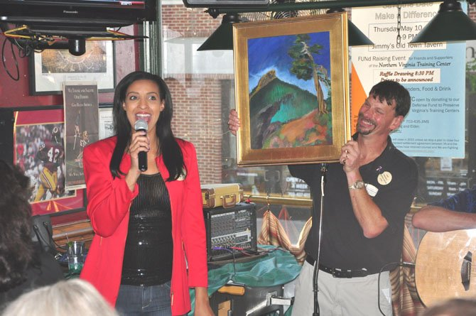Christy Winters Scott, South Lakes women's basketball coach and Washington Mystics commentator and Jimmy Cirrito, owner of Jimmy's Old Town Tavern, auction off a painting to raise money for the legal fund to try and keep the Northern Virginia Training Center open.