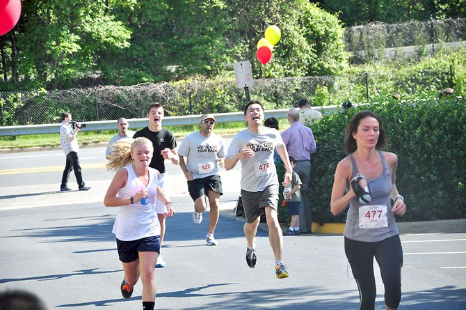"""Runners cross the finish line during the fifth annual """"We've Got Your Back"""" 5K in Reston Saturday, May 12, which raised more than $100,000 for the Spinal Research Foundation."""