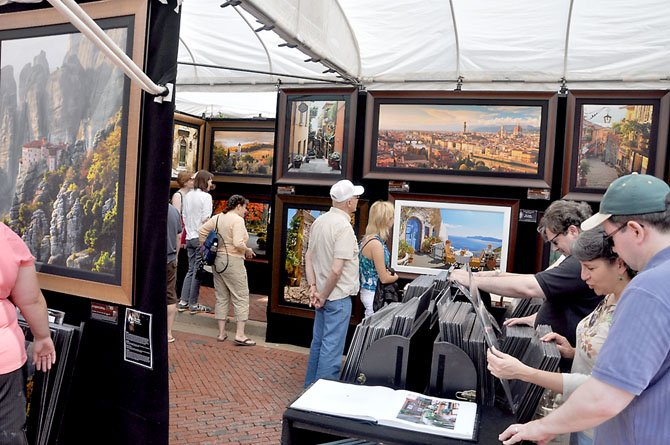 Visitors to the Northern Virginia Fine Arts Festival 2011 browse the work of John Scanlan, a photographer from Glenwood, Iowa.