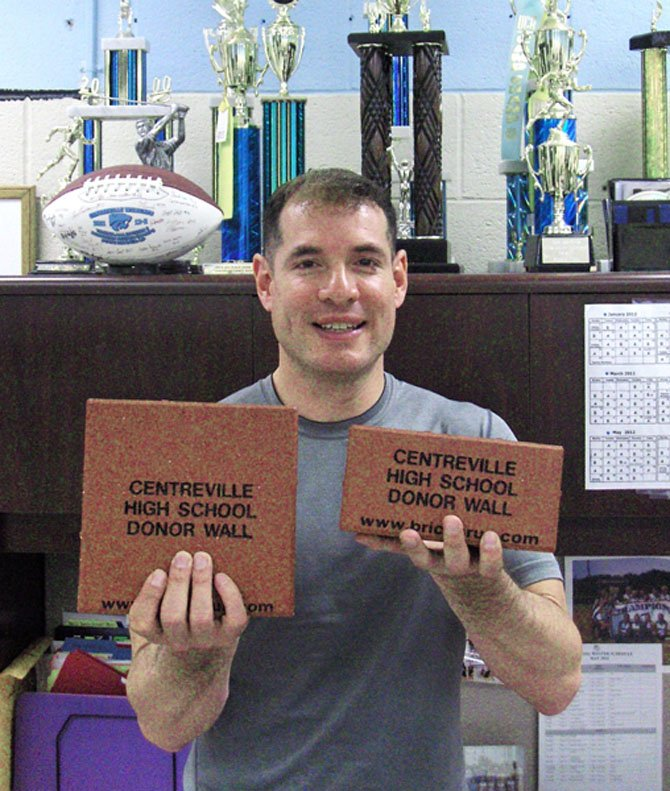 Centreville High Athletic Director Jimmy Sanabria holds examples of the bricks helping to fund artificial-turf fields for the school.