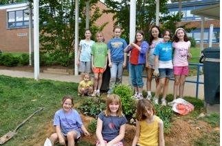 Girls from Brownie Troop 3352 and Junior Troop 2205 from Churchill Road School, admire the rain garden they created on the school's grounds. Pictured standing are: Simrin Jeddy, Molly Ferris, Lauren Hassi (Longfellow MS), Moppet Post, Nadia Jo, Rebecca Hassi, Phoebe Jeddy. Seated in front are: Megan Hassi, Alden Miller, Whitley Taylor. (Not pictured: Rachel Keiser, Kathryn Keiser, and Sahana Ramesh).