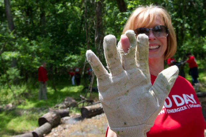 "Allene Murray of Keller Williams Realty of Chantilly/Centreville shows how she's ""worked through her gloves"" pulling invasive garlic mustard plants."