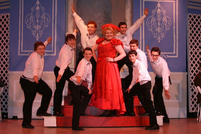 "Sean Pugerude, in the title role, is surrounded by the Waiters Ensemble in a number from Paul VI's musical, ""Hello, Dolly!"""