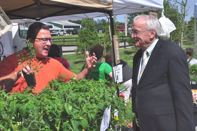 From left, Michael Anthony of Fossil Rock Farm speaks with USDA Under Secretary for Food, Nutrition and Consumer Services Kevin Concannon about the produce they offer at the Frying Pan Farm Park Farmer's Market Thursday, May 17.