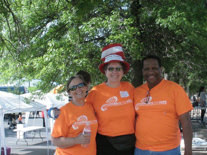 "From left, Holly Wieland, a volunteer and Registered Nurse of Herndon; Mary Ann Kral, who supports Connections for Hope on behalf of Vecinos Unidos, and Cornell Harris, a Consultant and Partner at WIPRO, who is on the Advisory Council of Connections for Hope and describes his role at the event as ""Parking Coordinator."""