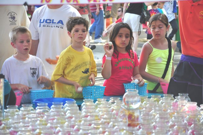 Children throw ping-pong balls for a chance to win goldfish at McLean Day, Saturday, May 19.