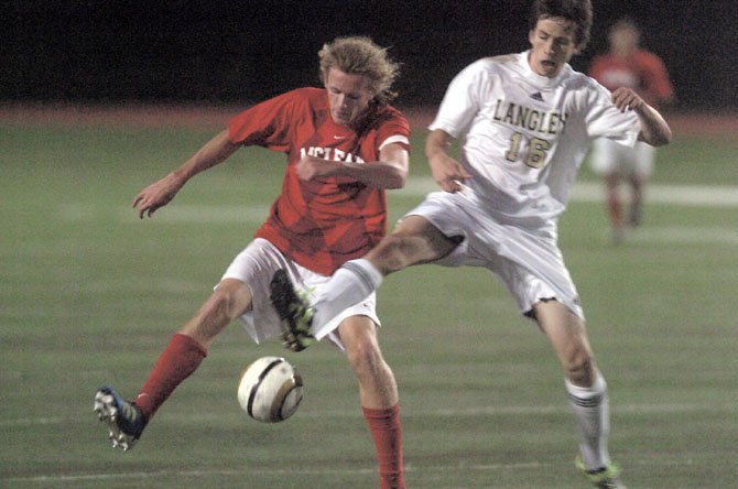 McLean's Mark Saunders works to keep the ball away from Langley's Roddy Haight during Friday night's Liberty District boys' soccer finals at Madison High School.