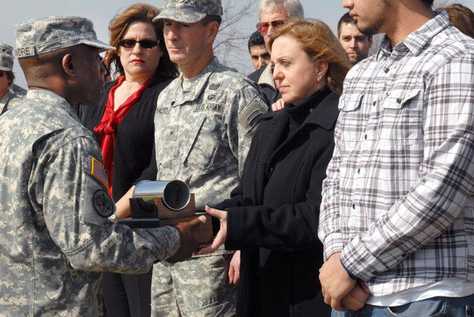 Command Sgt. Maj. Guitaud Leandre, 13th ESC, hands Cindy Hildner an artillery shell moments after it was fired from a cannon in her husband's honor at Fort Hood Feb. 9. Brig. Gen. Terence J. Hildner of Fairfax died in Afghanistan Feb. 3.