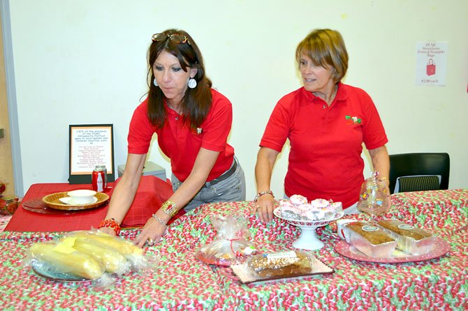Strawberry Festival bake sale co-chairs Joanne Ogilvie (left) and Suzanne Eastman organize a table of desserts. Proceeds from the event support the Potomac United Methodist Church's missions.