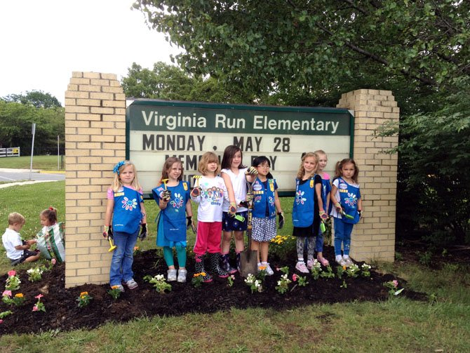 """Daisy Troop 3113 members at Virginia Run Elementary School has been working all year to earn 10 petals for their uniform which teaches them the Girl Scout law. This week the troop members earned their final petal — the pink petal which represents """"Make the world a better place."""" To make the world a better place, the girls planted pink, white and yellow flowers in the flower bed under the sign at Virginia Run Elementary School. One of the parents, Russel Ramey, edged the flower bed, cleared it of weeds and mulched it in preparation for the day. From left are Caroline Johnson, Eloise Latimer, Emily Bobek, Grace Ramey, Allison Nguyen, Sarah Van Buren, Ava Lawless and Ginny Fitch."""