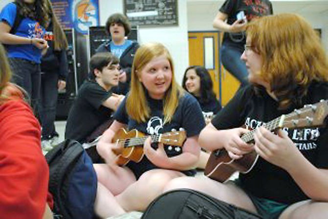 West Springfield students Maggie Rabe and CarrieWogaman (Choral Department) play guitar as the events opens on May 21.